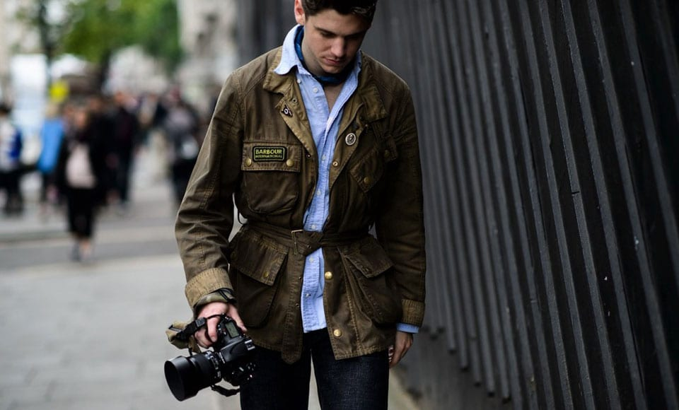 photographer walks holding camera wearing in barbour jacket - gillanders town and country