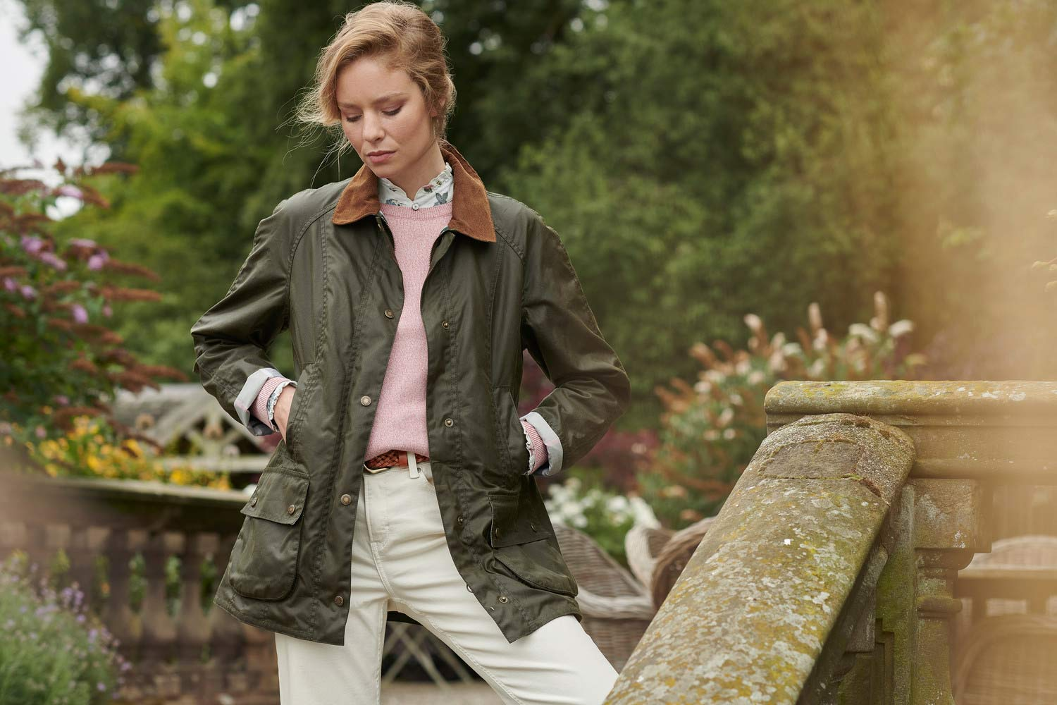 blonde woman stands on step on country house wearing Barbour Bowland Knit Barbour Bowland Shirt Barbour Aintree Wax
